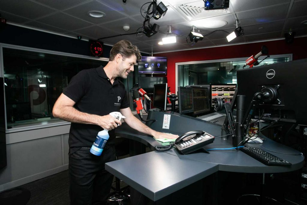 Priority One team member cleaning radio studio desk