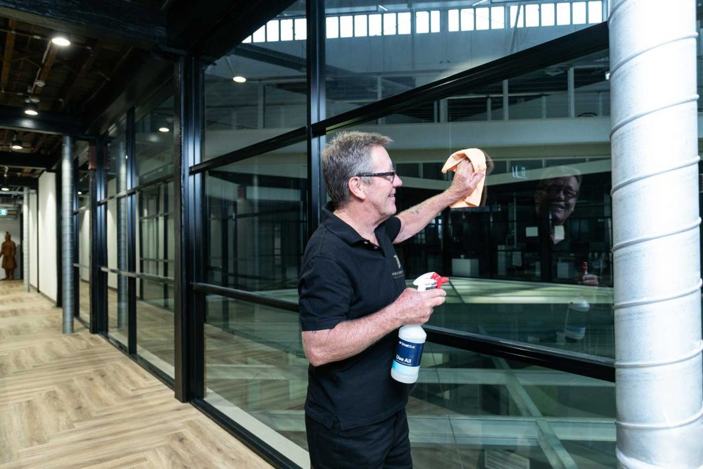 Priority One team member polishing commercial building glass
