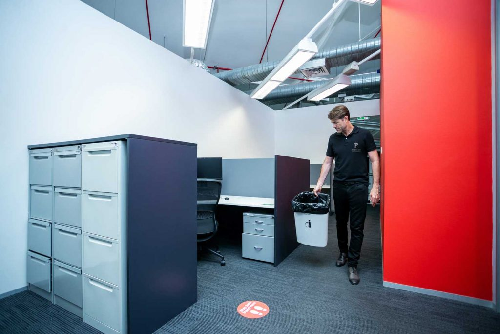 Priority One team member replacing waste bins in commercial office
