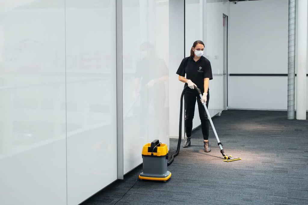 Priority One team member vacuuming office building floor